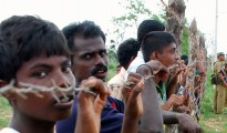 Civilians stand behind a barbed-wire fence as Sri Lankan soldiers stand nearby in the Menikfam Vanni refugee camp located near the town of Chettekulam in northern Sri Lanka