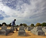A Tamil man sweeping at a mass cemetery of Tamil Tigers